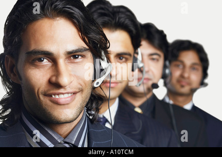 Porträt von vier männlichen Vertreter tragen headsets - Stockfoto