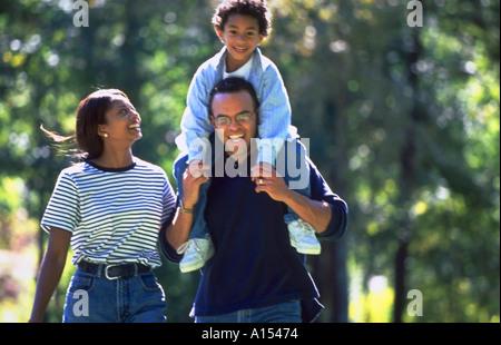 Eine afroamerikanische Familie im Park spazieren fährt der Sohn auf seinen Vater Schultern - Stockfoto