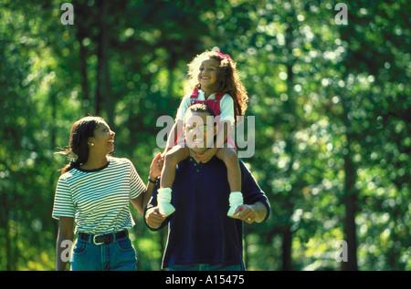 Eine afroamerikanische Familie im Park spazieren reitet die Tochter auf ihren Papa Schultern - Stockfoto