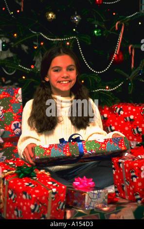 Porträt eines jungen Mädchens sitzen unter mehreren gewickelt Weihnachtsgeschenke vor einem Weihnachtsbaum - Stockfoto