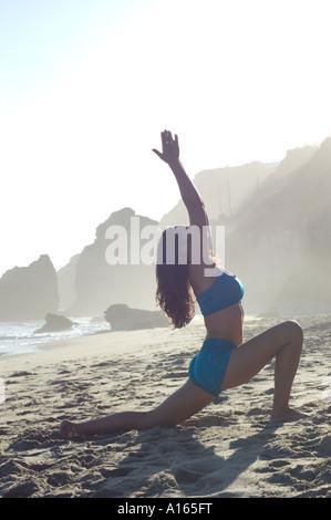 Junge Frau praktizieren Yoga am Strand - Stockfoto