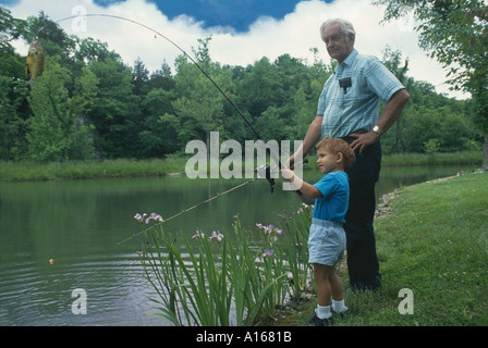 Erfolg! Großvater und Enkel gemeinsam einen Fisch auf einem iidylllic Tag auf einem Sommer Teich zu fangen, Midwest - Stockfoto
