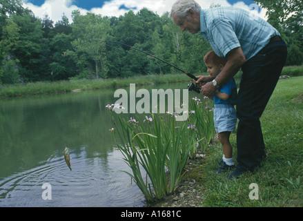 Erfolg! Ein Großvater und Enkel einen kleinen Fischen zusammen in einem Teich, Midwest USA - Stockfoto