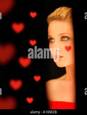 Porträt einer jungen Frau 18, 19, 20, 21, 20-24, 24-29, 30-34, Jahre alt mit rotem Herz auf der Wange - Stockfoto
