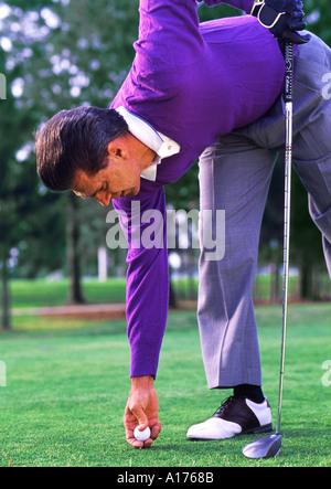 Gut gekleideter Mann Platzierung Golfball auf tee - Stockfoto