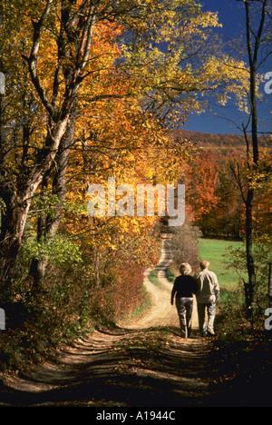 Älteres Paar zu Fuß entlang der unbefestigten Straße gesäumt von Herbstfarben - Stockfoto