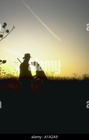 Silhouette der Fasan Jäger und seinem Hund in einem Feld bei Sonnenaufgang - Stockfoto