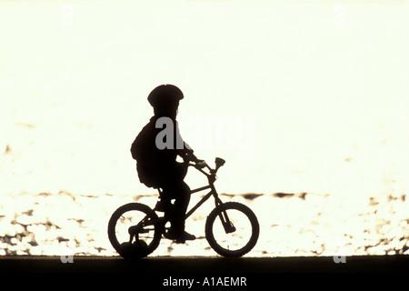 USA, Washington, Seattle, Sommer Sonne Silhouetten junge Radfahrer entlang reiten trail rund um Green Lake Park - Stockfoto