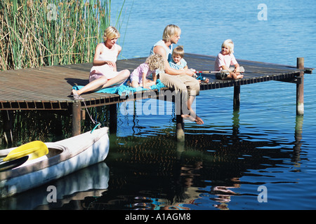 Familie sitzt auf einem Steg - Stockfoto