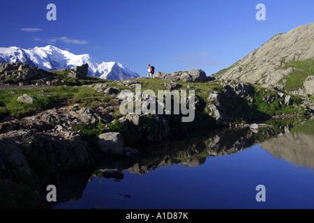 Fernen weibliche Wanderer in den französischen Alpen mit dem Mont-Blanc-Massiv im Hintergrund - Stockfoto
