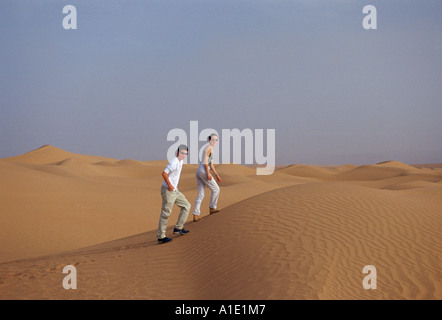 Junger Mann und Frau Fuß bis Sanddünen in der Sahara Wüste Marokko - Stockfoto