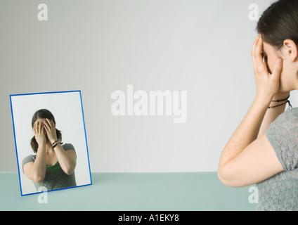 Junge Frau vor Spiegel mit Händen über Gesicht - Stockfoto