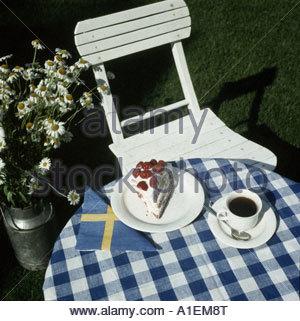 Ein Stück Erdbeerkuchen und eine Kaffeetasse auf einem Gartentisch - Stockfoto