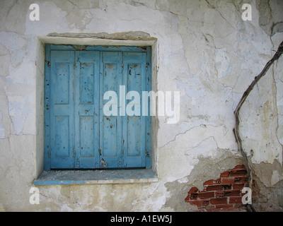 Blauen Fensterläden Fenster in beschädigten weiße Wand mit crack auszusetzen rote Ziegeln - Stockfoto