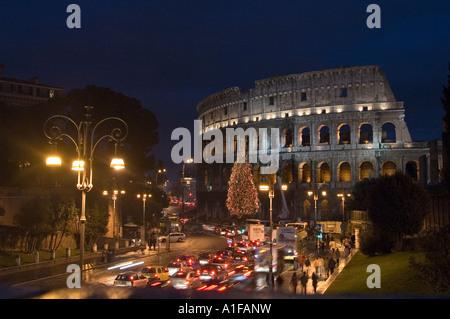 Außenansicht des Amphitheaters Kolosseum bei Nacht beleuchtete Weihnachtsbaum mit Ampeln, Rom Italien - Stockfoto