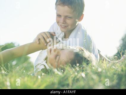 Jungen und Mädchen spielen in Rasen Stockfoto