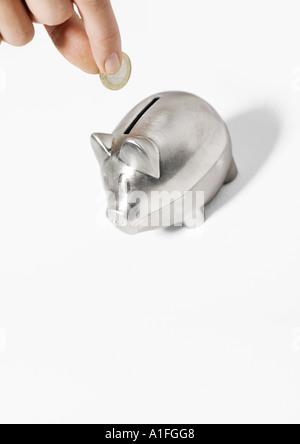Hand Sparschwein Münze einfügen - Stockfoto