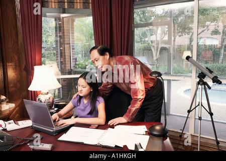 Mädchen mit einem Laptop mit ihrem Großvater neben ihr Stand - Stockfoto