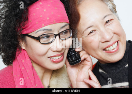 Porträt einer reifen Frau mit ihren Freunden, die mit dem Handy telefonieren - Stockfoto