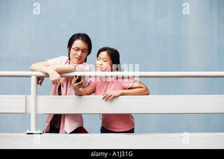 Junge Frau und ein Mitte erwachsenen Mannes Blick auf ein Mobiltelefon - Stockfoto