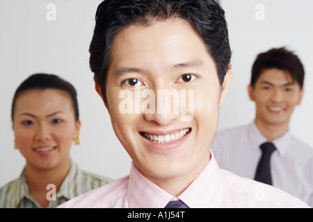 Porträt eines Geschäftsmannes lächelnd mit seinen Kollegen im Hintergrund - Stockfoto