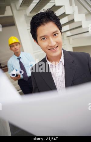Porträt eines Geschäftsmannes holding Blaupausen und lächelnd - Stockfoto