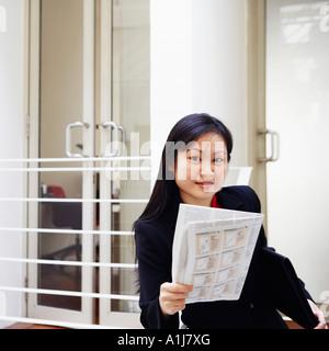 Porträt einer Geschäftsfrau hält eine Zeitung und lächelnd - Stockfoto