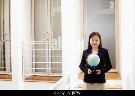 Porträt einer Geschäftsfrau hält einen Globus und lächelnd - Stockfoto