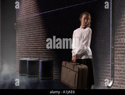 Kaukasische Teengirl Runaway stehend in dunklen Gasse mit Koffer USA - Stockfoto