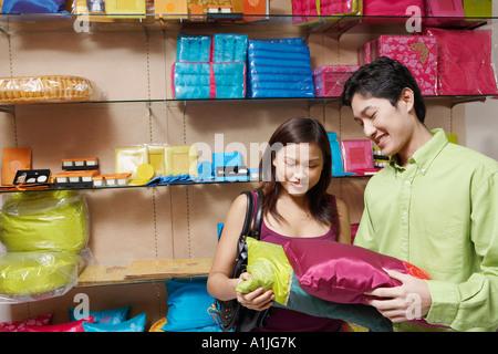 Nahaufnahme eines jungen Paares Wahl Kissen in einem Geschäft und lächelt - Stockfoto