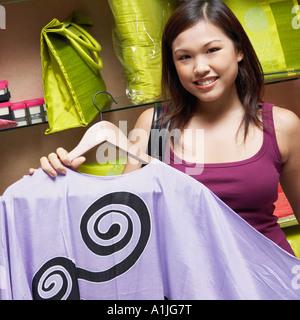 Porträt einer jungen Frau die Wahl einer Kleid in einem Geschäft und lächelt - Stockfoto