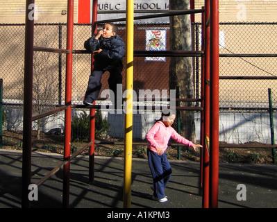 Hispanic jungen und Mädchen spielen auf dem Spielplatz Turnhalle Bars, New York City, USA - Stockfoto