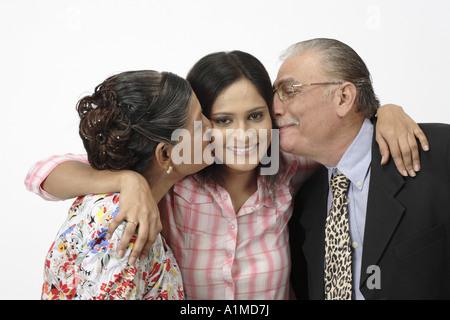 Familie von indischer Staatsbürger paar Mann Frau küssen Tochter auf Wangen - Stockfoto