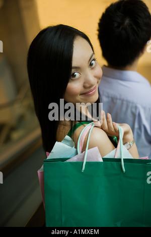 Junge Frau, die Einkaufstaschen tragen - Stockfoto