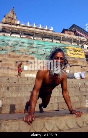 Ein Mann-Übungen am Ufer des heiligen Flusses Ganges in der Stadt Varanasi in Nordindien - Stockfoto