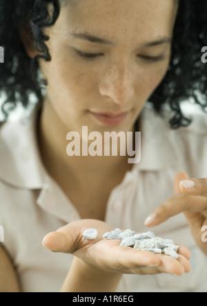 Frau blickte auf Stücke von Kies statt auf Handfläche - Stockfoto
