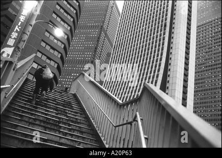 Ein Mann geht nach oben in die Wolkenkratzer Geschäft Bezirk von Nishi Shinjuku, Tokio, Japan. - Stockfoto