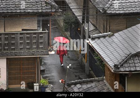 Frau trägt einen roten Kimono und tragen einen roten Regenschirm geht durch den Regen in den alten Straßen von Gion - Stockfoto