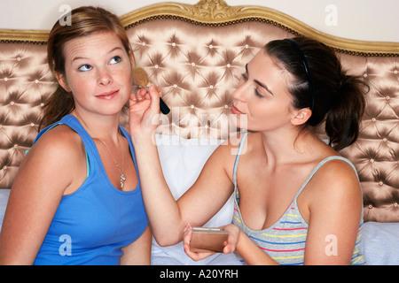 Teenager-Mädchen sitzen auf Bett, Gesicht Freundes erröten zuweisen - Stockfoto
