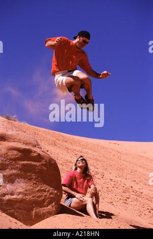 Ein Mann über eine Frau auf einer Sanddüne in Moab Utah springen - Stockfoto