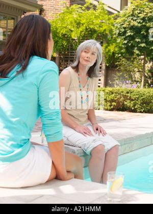Frauen sitzen am Beckenrand Stockfoto