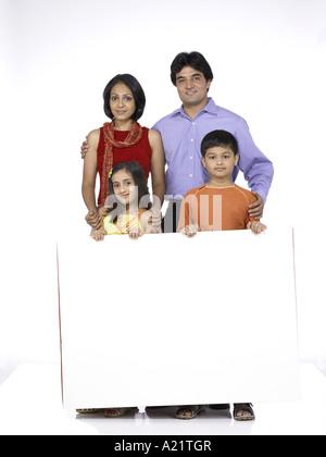 Südasiatische indische Familie mit Vater Mutter Sohn und Tochter stand lächelnd halten weiße Farbe board - Stockfoto