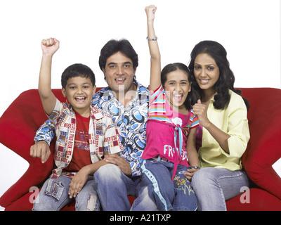 Südasiatische indische Familie mit Vater Mutter Sohn und Tochter sitzen auf dem Sofa zu Lächeln - Stockfoto