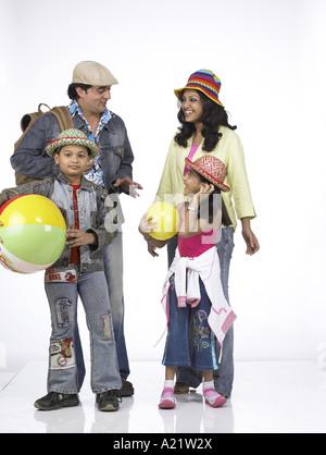 Südasiatische indische Familie mit Vater Mutter Sohn und Tochter stand lächelnd - Stockfoto