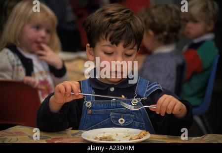 Kind mit Messer und Gabel für Schule Abendessen - Stockfoto