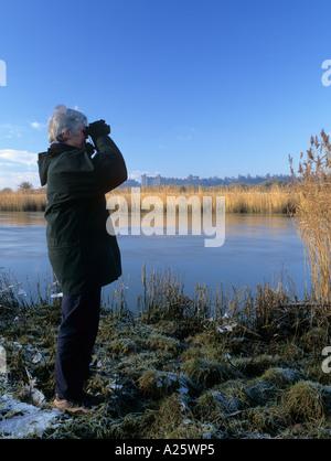 Vogelbeobachter mit dem Fernglas durch Fluss Arun im Winter.  Warningcamp Arundel West Sussex England UK - Stockfoto
