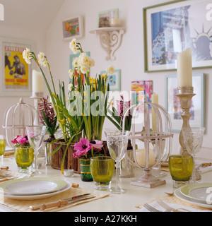 Gedeckter Tisch mit Narzissen und Kerzen in Londoner Stadthaus dekoriert - Stockfoto