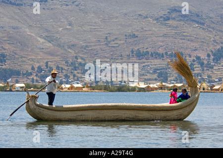 Ein Vater und 2 Kinder gekleidet in traditioneller Kleidung auf einem traditionellen Reed-Boot auf dem Titicacasee. - Stockfoto