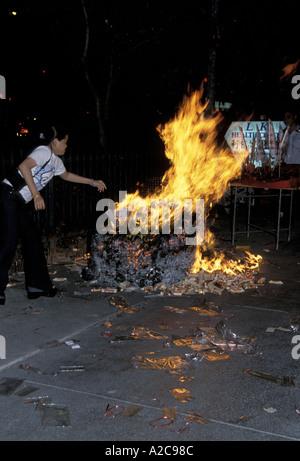 Eine Frau, die während des Festivals des hungrigen Geistes Papiergeld in ein Lagerfeuer in Singapur zu werfen - Stockfoto
