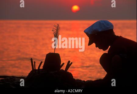 ein kleiner Junge eine Sandburg bauen bei Sonnenuntergang am Strand von Katy Rybackie bei Danzig in Polen - Stockfoto